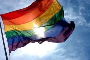 1280px-Rainbow_flag_and_blue_skies